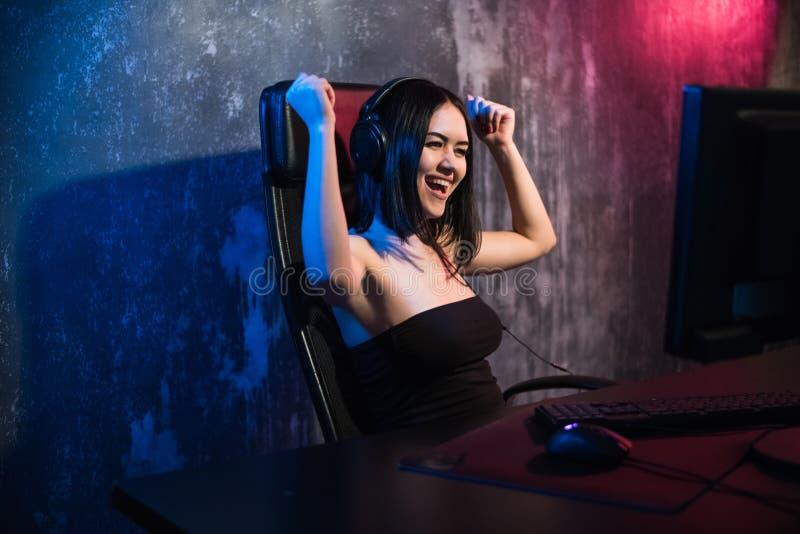 Gelukkig vrolijk leuk sexy de handgebaar van het gamermeisje van winst en zuivere emotie Zittend thuis het spelen videospelletjes stock fotografie