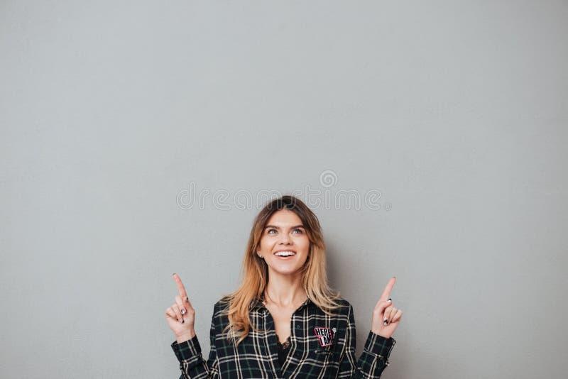 Gelukkig vrolijk meisje die twee vingers benadrukken op exemplaarruimte stock afbeeldingen