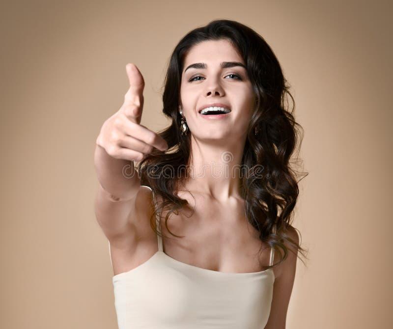 Gelukkig vrolijk meisje die vinger richten op geïsoleerde camera stock afbeeldingen