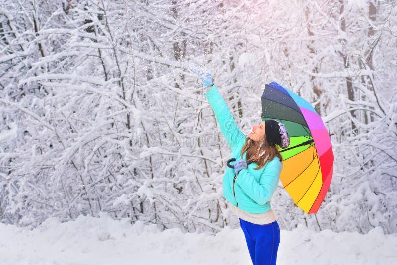 Gelukkig vrolijk meisje met een regenboogparaplu op een de winter bosachtergrond royalty-vrije stock afbeeldingen