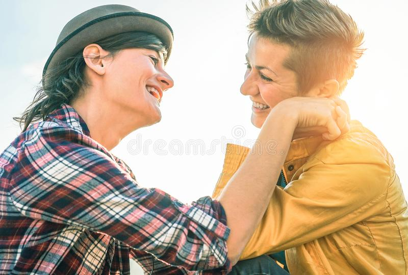 Gelukkig vrolijk paar die elkaar bekijken te overhandigen hand - Jonge vrouwenlesbiennes die een teder ogenblik hebben openlucht royalty-vrije stock foto