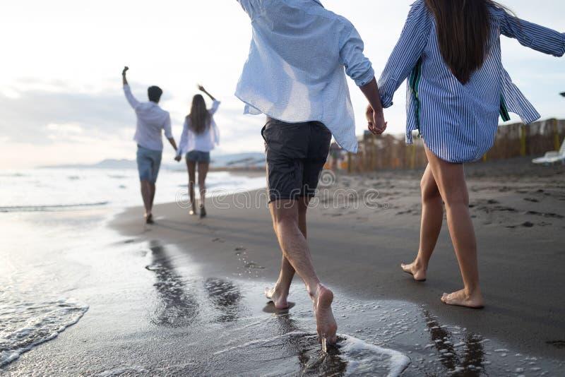 Gelukkig vrolijk paar die pret op een tropisch strand hebben bij zonsondergang stock fotografie