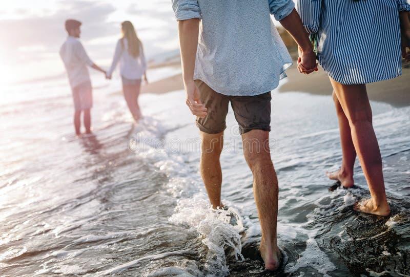 Gelukkig vrolijk paar die pret op een tropisch strand hebben bij zonsondergang royalty-vrije stock fotografie