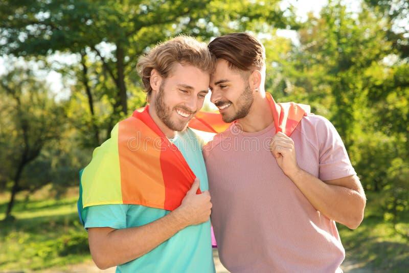 Gelukkig vrolijk paar met regenboogvlag royalty-vrije stock afbeelding