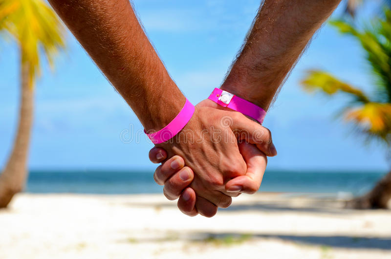 Gelukkig vrolijk paar op de handen van de strandholding stock foto