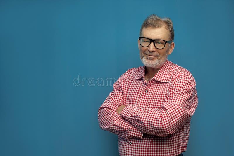 Gelukkig vrolijk zeker bejaarde die rood overhemd en modieuze oogglazen dragen royalty-vrije stock fotografie