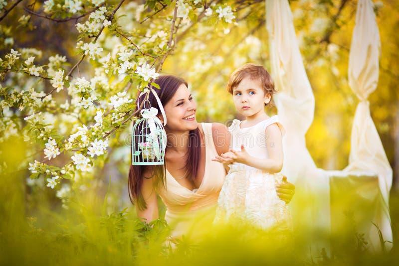 Gelukkig vrouw en kind in de bloeiende de lentetuin. Kindkissi royalty-vrije stock afbeeldingen