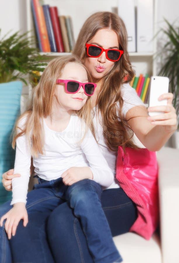 Gelukkig vrouw en kind die een selfie nemen stock fotografie