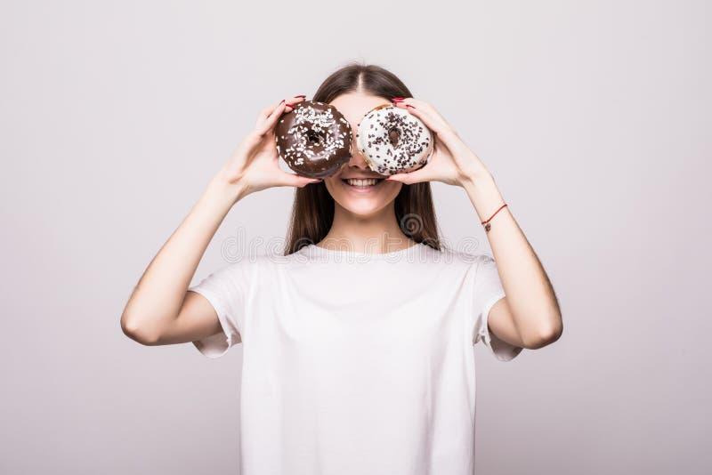 Gelukkig vrouw of tienermeisje die door donuts op grijze achtergrond kijken Het concept van de gezondheid royalty-vrije stock afbeeldingen