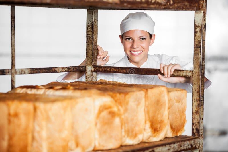 Gelukkig Vrouwelijk Baker Pushing Bread Rack royalty-vrije stock afbeeldingen