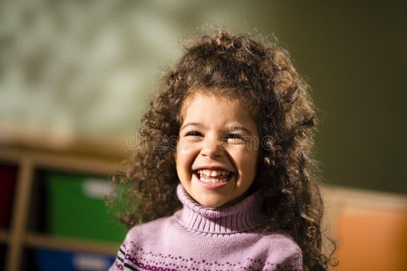 Gelukkig vrouwelijk kind dat voor vreugde in kleuterschool glimlacht royalty-vrije stock foto's