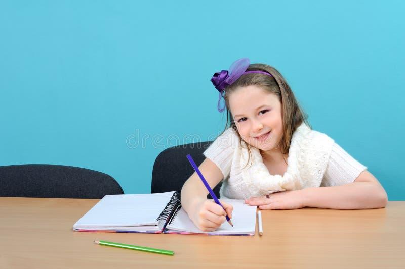 Gelukkig vrouwelijk schoolkind dat haar schoolwerk doet stock afbeelding