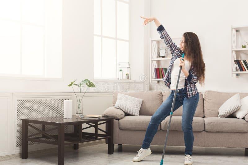 Gelukkig vrouwen schoonmakend huis met zwabber en het hebben van pret royalty-vrije stock foto