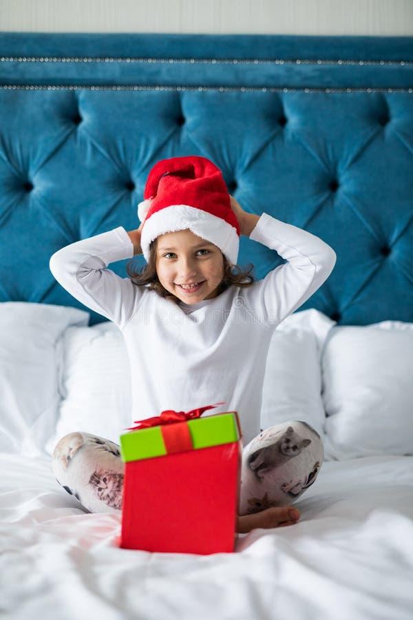 Gelukkig weggegaan meisje in de doos van de de holdingsgift van de Kerstman` s hoed, die opgewekte camera bekijken terwijl het zi stock foto
