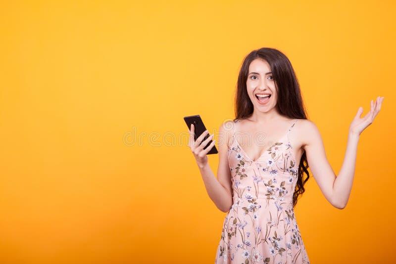Gelukkig weggegaan mooi meisje die in korte kleding mobiele telefoon houden stock afbeelding