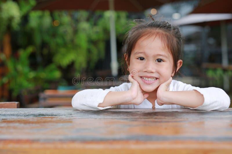 Gelukkig weinig Aziatisch jong geitjemeisje die op de houten lijst met het kijken liggen camera stock foto