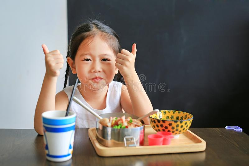 Gelukkig weinig Aziatisch jong geitjemeisje die rijst eten door zelf in het restaurant stock foto
