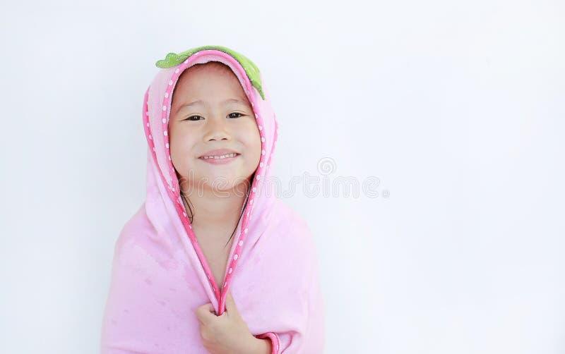 Gelukkig weinig Aziatisch kindmeisje die onder handdoek na badzitting glimlachen op witte achtergrond royalty-vrije stock afbeeldingen