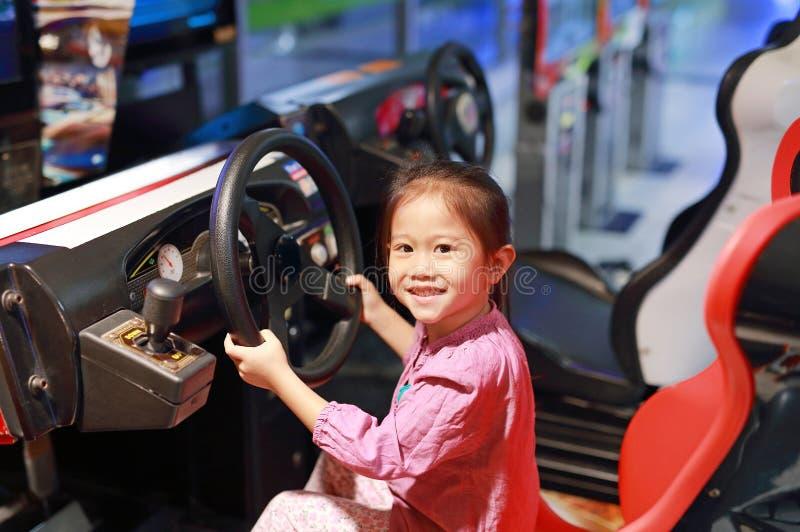 Gelukkig weinig Aziatisch kindmeisje het spelen arcadevideospelletje Het rennen auto stock fotografie