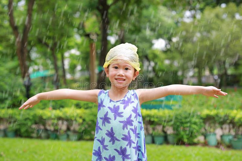 Gelukkig weinig Aziatisch meisje die plastic zaknoodsituatie GLB op hoofd dragen die pret in de de zomerregen hebben stock fotografie