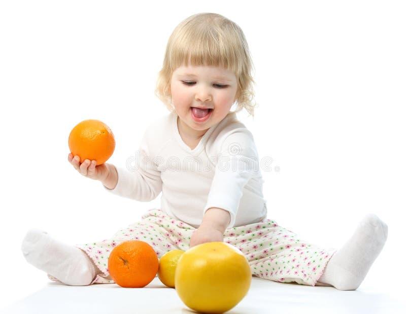 Gelukkig weinig baby die met vruchten speelt stock foto's