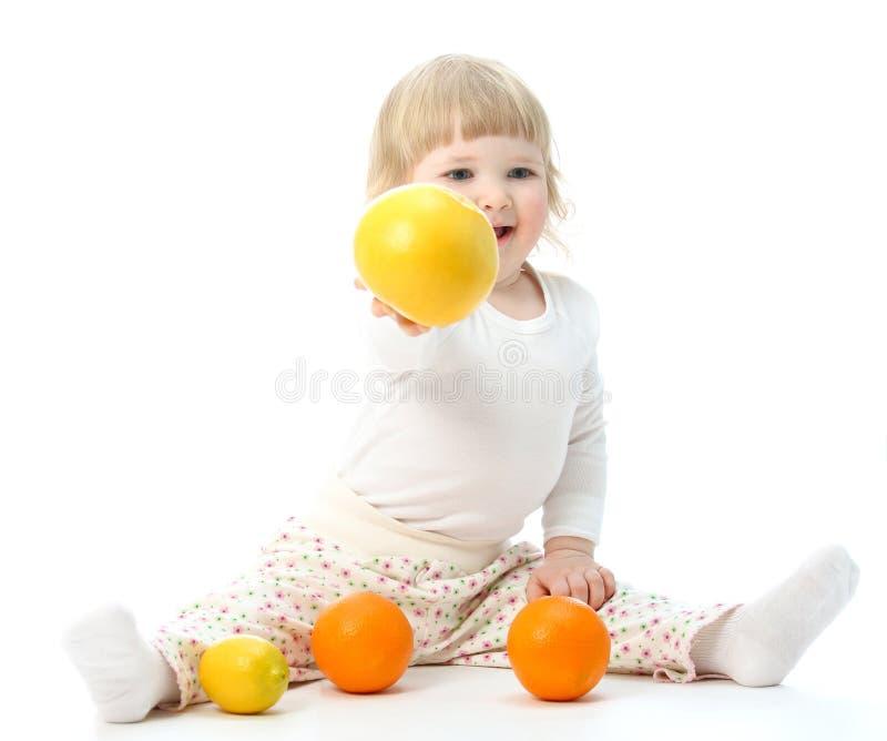 Gelukkig weinig baby met vruchten stock foto