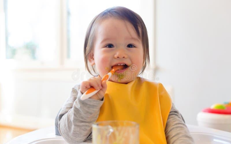 Gelukkig weinig babyjongen die voedsel eten royalty-vrije stock fotografie