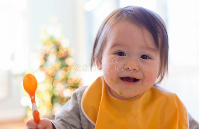 Gelukkig weinig babyjongen die voedsel eten stock fotografie