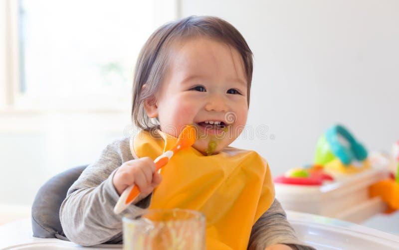 Gelukkig weinig babyjongen die voedsel eten stock foto's