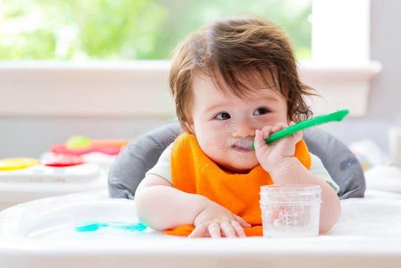 Gelukkig weinig babyjongen die voedsel eten stock afbeelding