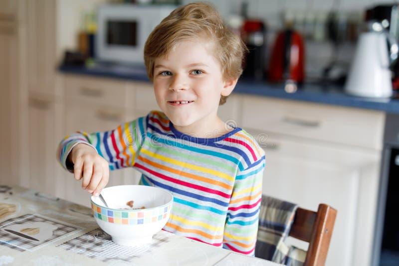 Gelukkig weinig blonde jong geitjejongen die graangewassen voor ontbijt of lunch eten Het gezonde eten voor kinderen stock afbeelding