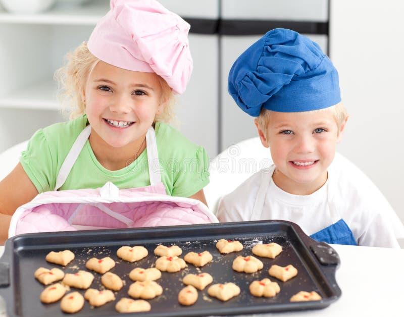 Gelukkig weinig broer en zuster met koekjes royalty-vrije stock afbeeldingen