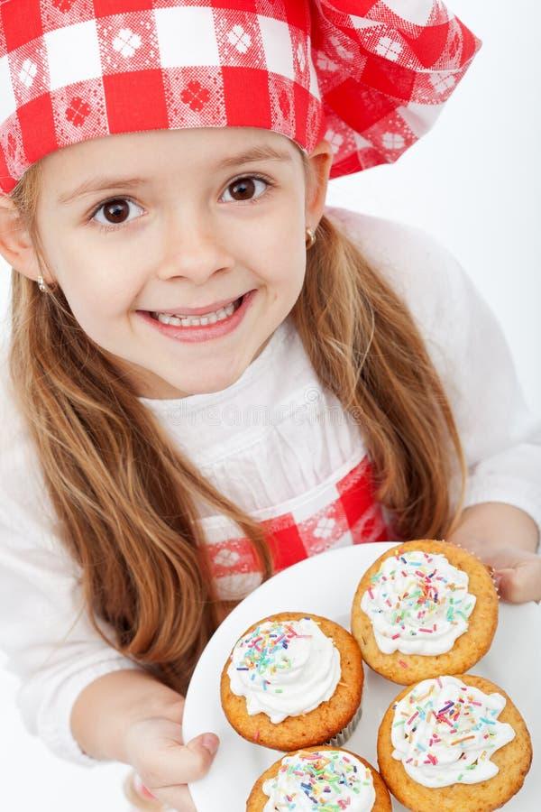 Gelukkig weinig chef-kok trots van haar muffins stock foto