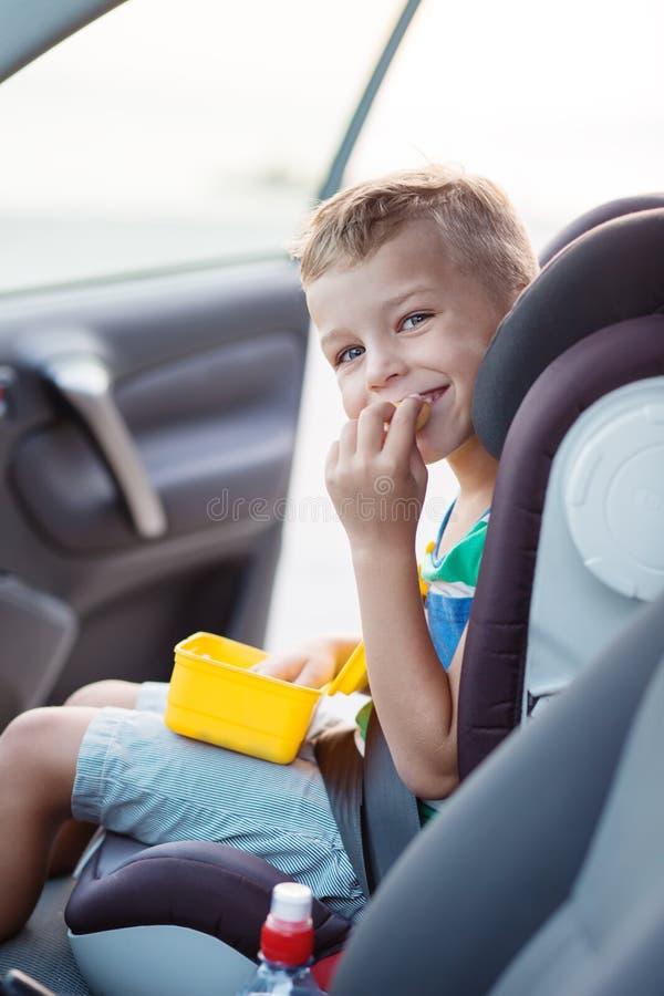 Gelukkig weinig jongen in auto het eten royalty-vrije stock afbeeldingen
