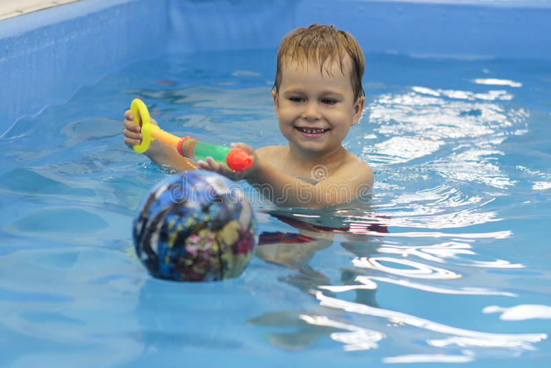 Gelukkig weinig jongen die in de pool speelt royalty-vrije stock foto