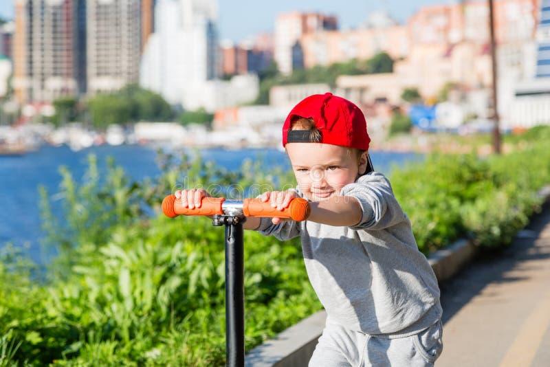Gelukkig weinig jongen die een autoped berijden op de dijk royalty-vrije stock afbeelding