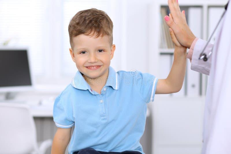 Gelukkig weinig jongen die hoogte vijf na gezondheidsexamen geven op artsen` s kantoor royalty-vrije stock afbeelding