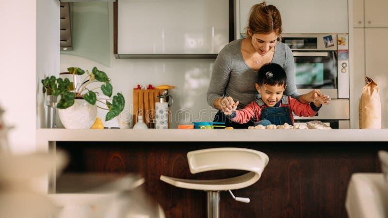 Gelukkig weinig jongen die koekjes met moeder maken stock fotografie