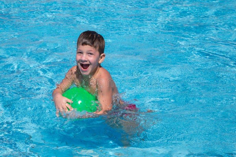 Gelukkig weinig jongen die met bal in de pool spelen royalty-vrije stock afbeeldingen