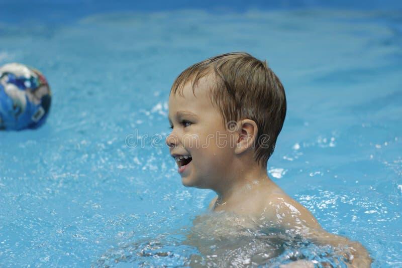 Gelukkig weinig jongen die met bal in de pool spelen royalty-vrije stock foto's