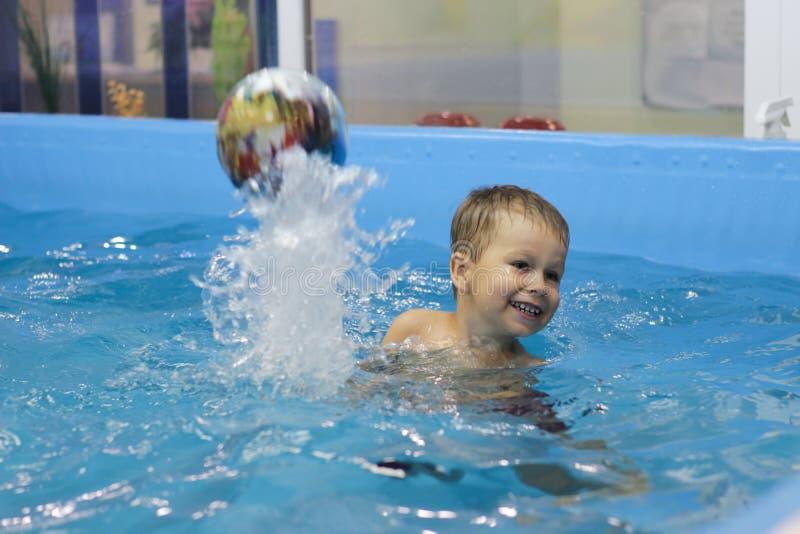 Gelukkig weinig jongen die met bal in de pool spelen royalty-vrije stock fotografie