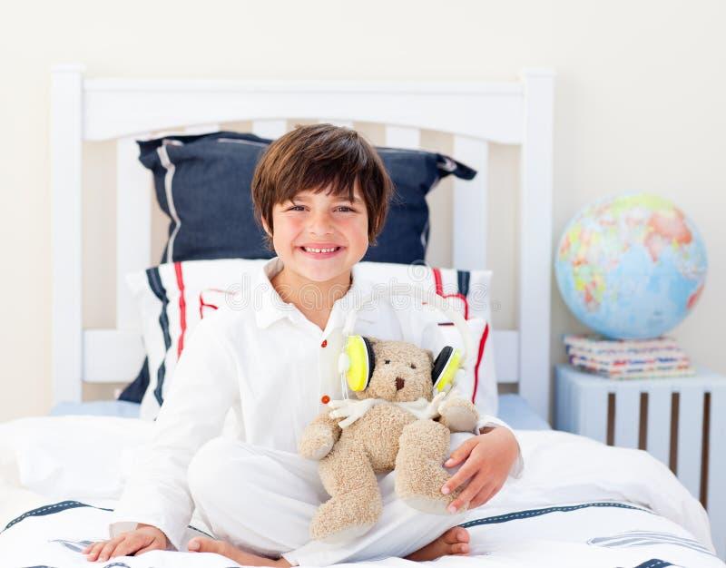 Gelukkig weinig jongen die met een teddybeer speelt stock afbeeldingen