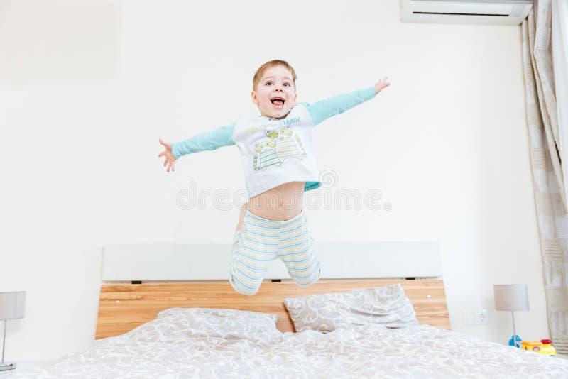 Gelukkig weinig jongen die op bed springen royalty-vrije stock afbeeldingen