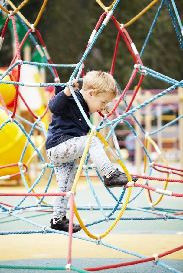 Gelukkig weinig jongen die op speelplaatsmateriaal beklimmen royalty-vrije stock afbeeldingen