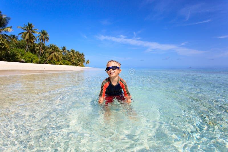 Gelukkig weinig jongen die op tropisch strand zwemt royalty-vrije stock afbeelding