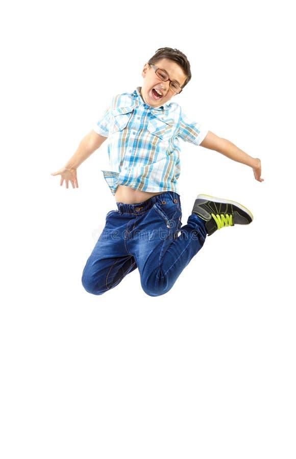 Gelukkig weinig jongen die op wit springen stock foto