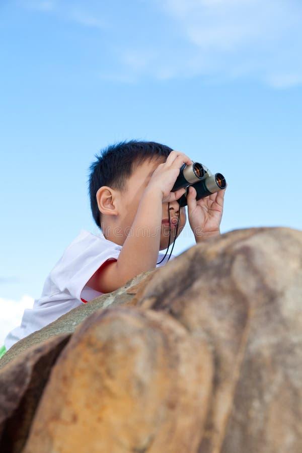 Gelukkig weinig jongen die in openlucht het klauteren op een rots met te onderzoeken royalty-vrije stock fotografie