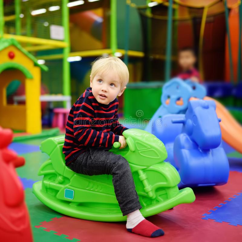 Gelukkig weinig jongen die pret met plastic speelgoed-schommeling/hoppenmotor in spelcentrum hebben royalty-vrije stock foto