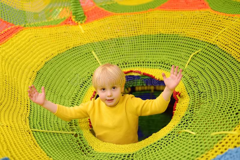 Gelukkig weinig jongen die pret in vermaak in spelcentrum hebben Kind het spelen op binnenspeelplaats stock afbeeldingen