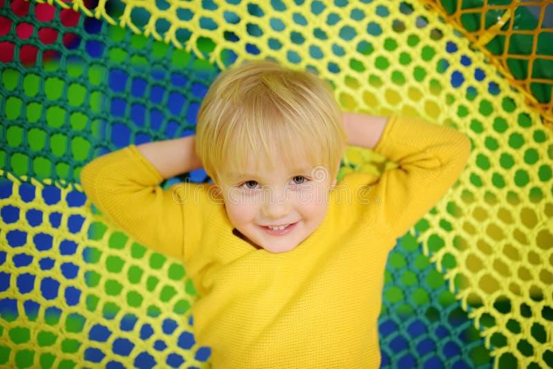 Gelukkig weinig jongen die pret in vermaak in spelcentrum hebben Kind het spelen op binnenspeelplaats royalty-vrije stock foto's